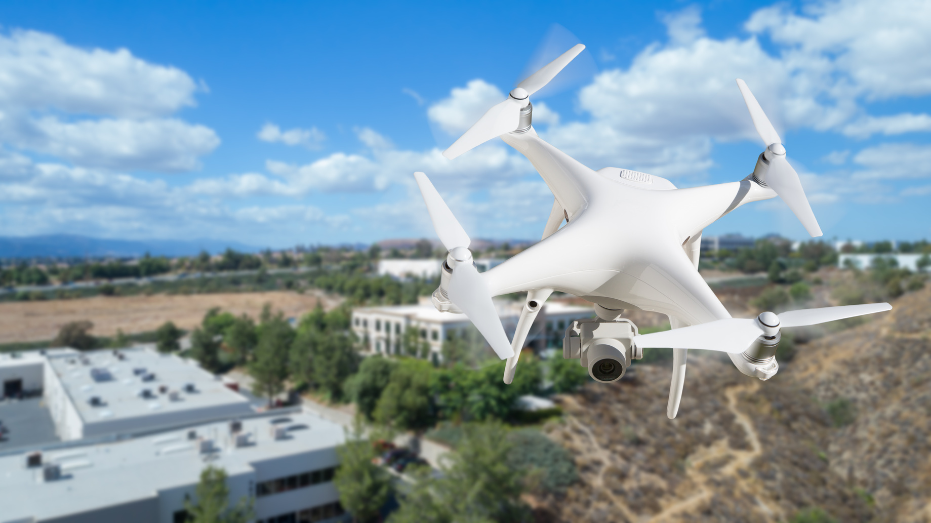 Unmanned Aircraft System (UAV) Quadcopter Drone In The Air Over Commercial Buildings. emerging technology on commercial real estate